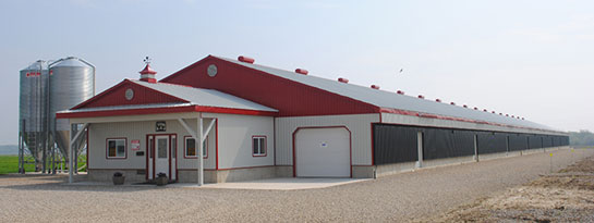 Image of a red and white building with two silos beside the building