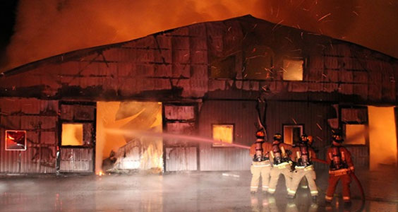 A photograph of four fireman directing a stream of water from a firehose into horse barn fully engulfed in flames.