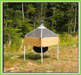 Picture of a horse fly trap. It contains a small tent shaped structure beneath which hangs a black ball shaped object.