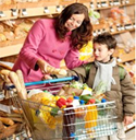 A woman and a child in front of a grocery cart in the bakery section of a grocery store. The woman is putting a baguette in the cart.