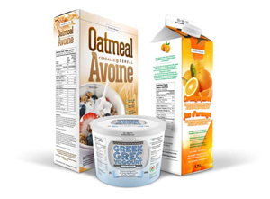 A 500 grams container of Greek yogourt at the front with a box of oatmeal cereal to the left and a 1.25 litre carton of orange juice to the right.