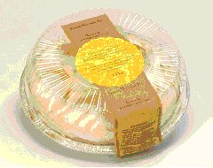 This is the top view of a cake is in rigid plastic packaging. Although there are ridges along the side of the lid, there is a raised area that can support a label. The ridging on the sides can usually support a label.