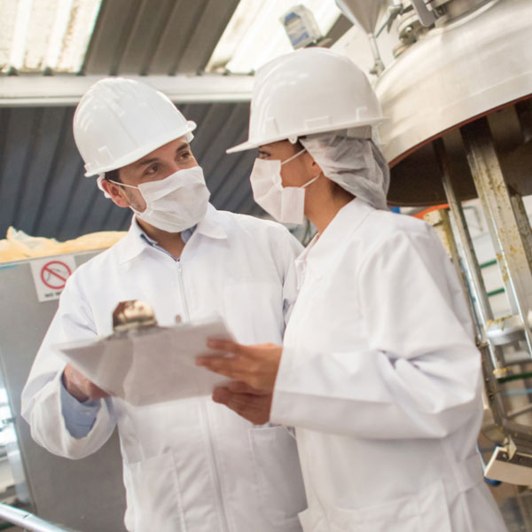 Two inspectors are in a food manufacturing facility. They are in protective equipment and holding a clipboard.
