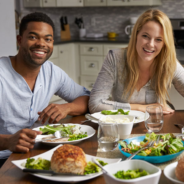 A family of three is eating dinner at their kitchen table.