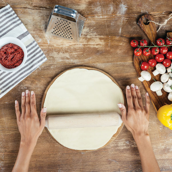 Two hands are rolling out pizza dough. Around the dough there is cheese, tomato sauce, and ingredients needed to make a pizza.