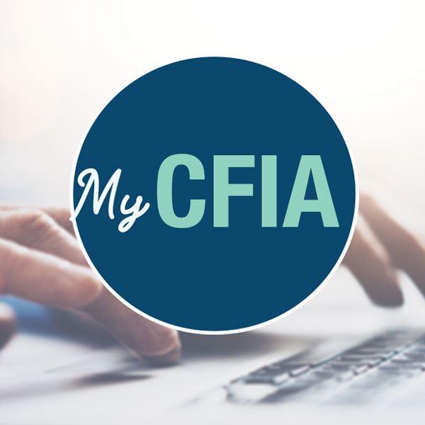 Two hands are typing on a laptop that is displaying the My CFIA sign up page.