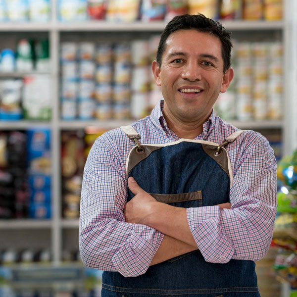 A small business owner standing inside his grocery store with his arms across his chest and a big smile on his face. Behind him are shelves filled with groceries.