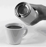 Image of someone pouring sirop from the tin can into a cup of coffee.