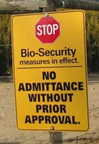 A biosecurity sign on a post in a field. Description follows.